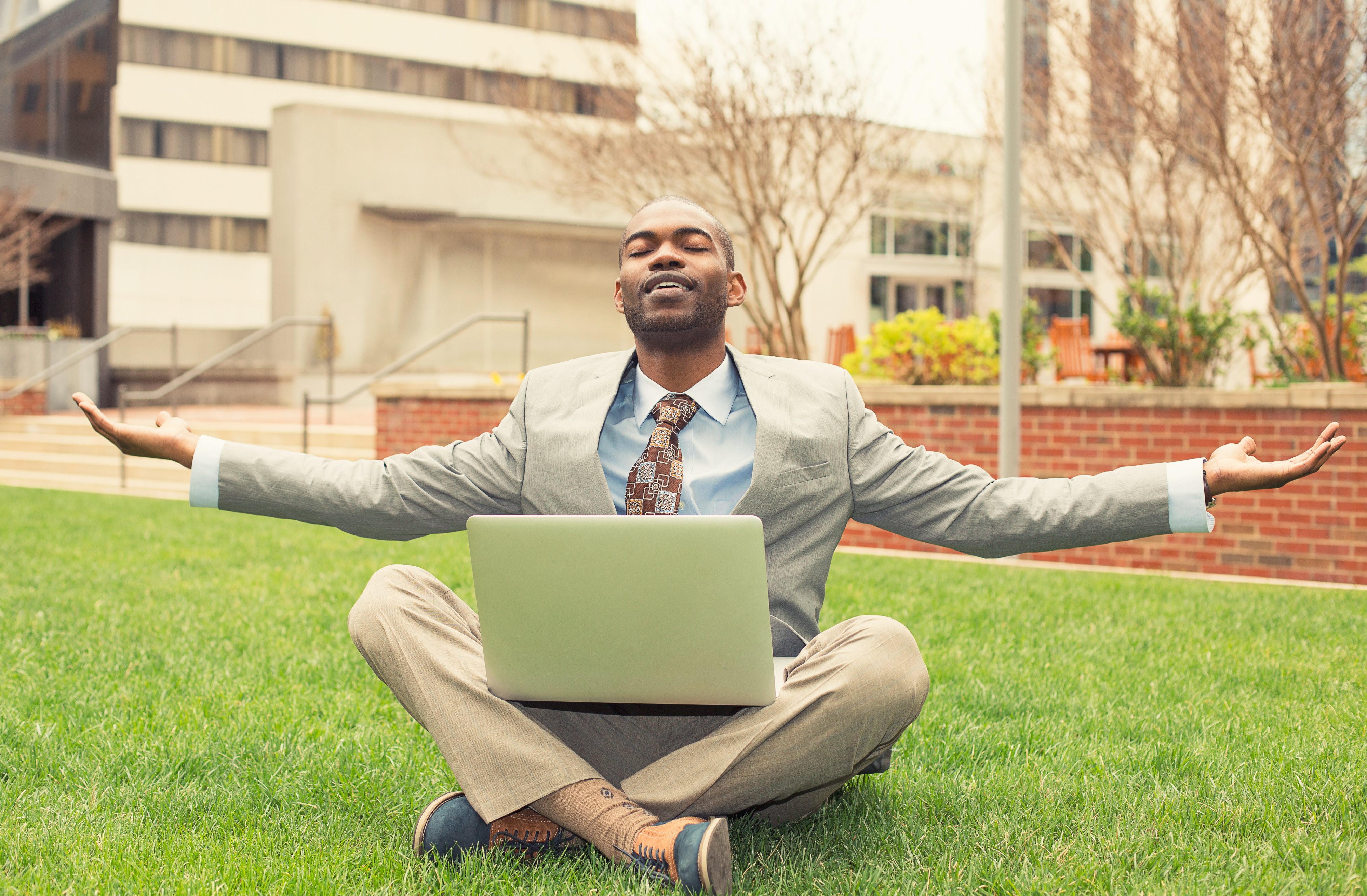 Young businessman with computer relaxing outside corporate office sitting on green grass in mediation mode